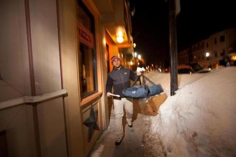 2/21/15 Dorchester, MA -- Deliveryman Johnson Cledanor walks a delivery to his car outside Pantry Pizza in Dorchester, February 21, 2015. Erik Jacobs for the Boston Globe