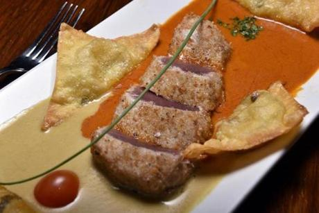 Pan-seared tuna in chile cream sauces, served with crisp ravioli filled with pear.