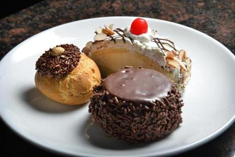 Clockwise from top, rollo, of coconut, ricotta, whipped cream and almonds, Italian chocolate mousse, and Nutella filled bocconcini, from the rotating assortment of pastry offered, at Brelundi Restaurant abutting the Waltham commuter rail station. Josh Reynolds for The Boston Globe (Lifestyle, bhange)