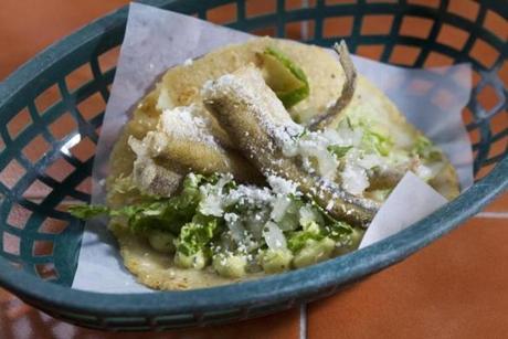 Fish taco, made of a whole fried smelt, cabbage, avocado, and tomatillo crema.