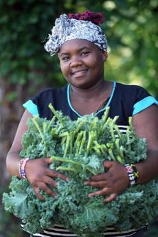 Kenyan Henrietta Nyaigoti grabs kale.