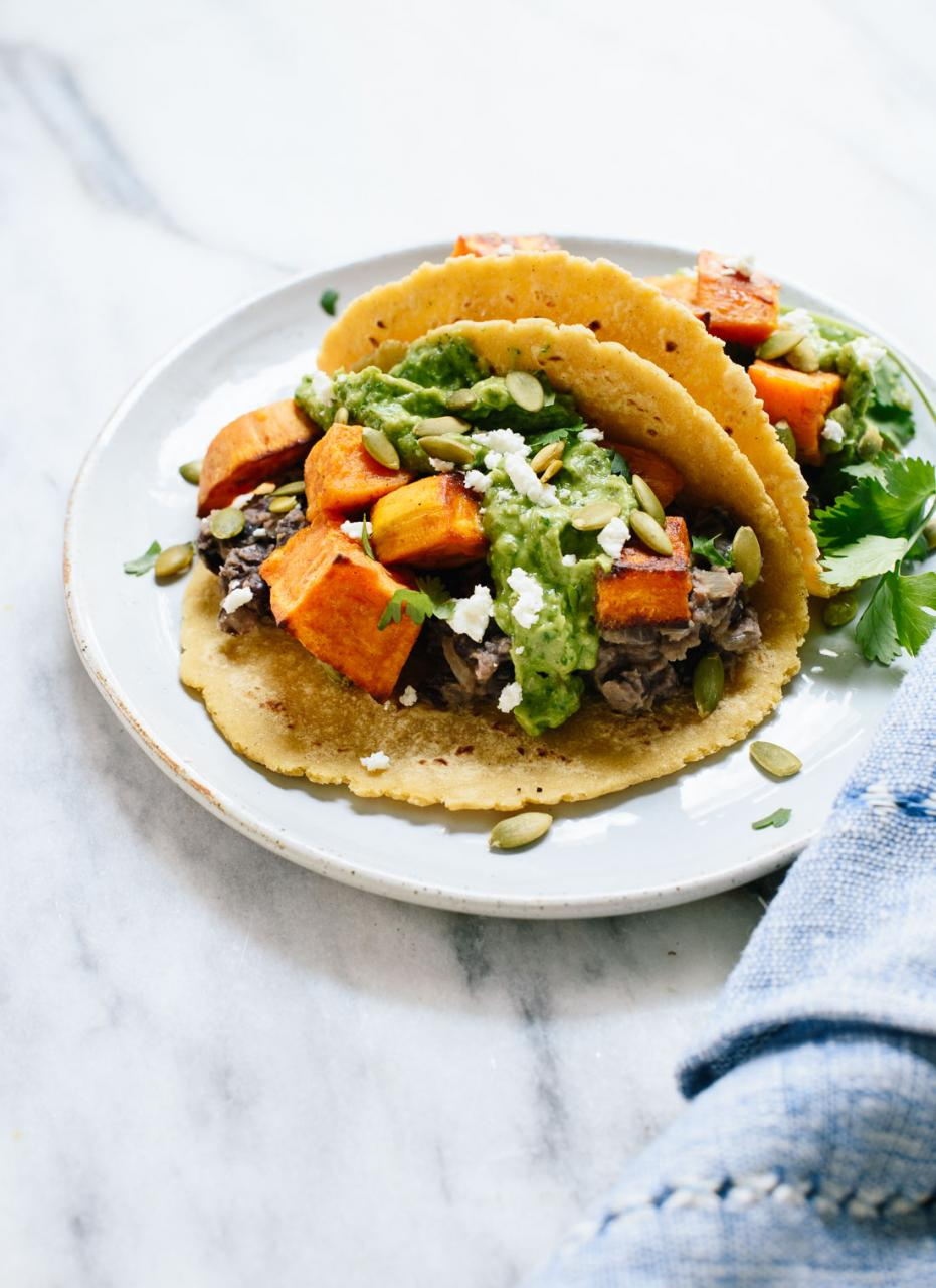 These roasted sweet potato tacos feature spicy black beans and avocado-pepita dip. Delicious! This taco recipe is vegetarian (easily vegan) and gluten-free. cookieandkate.com
